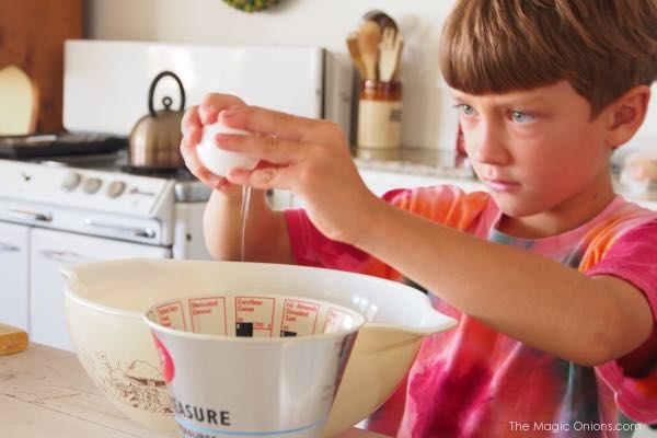 photo of a kid cracking an egg to make a cake recipe